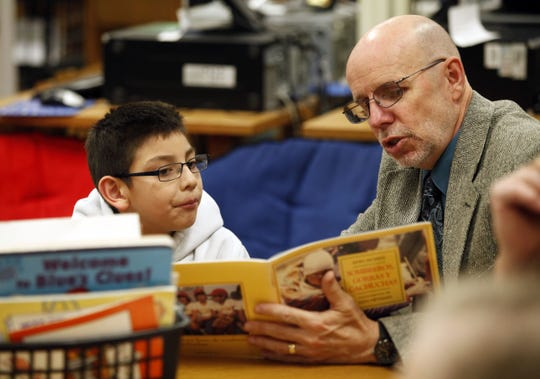 Carlos Aguilar, 7, listens to a story as he finishes eating his lunch with Everybody Wins! Iowa mentor Craig Burton at River Woods Elementary School  in 2013.
