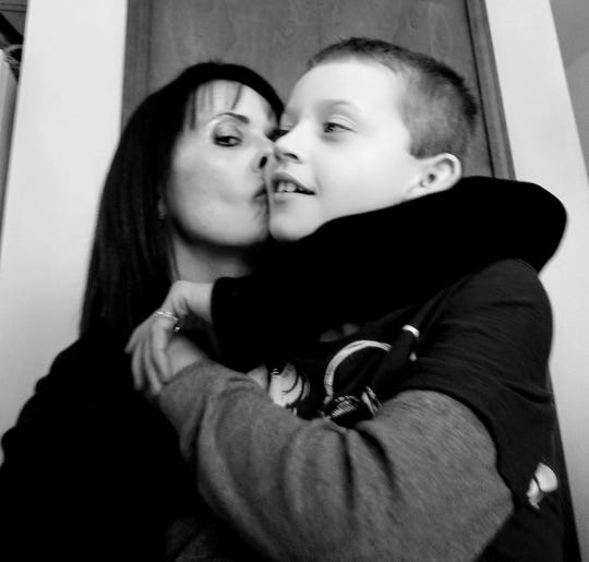 Tina Talbot kisses her son, Phillip, who has autism and is nonverbal.