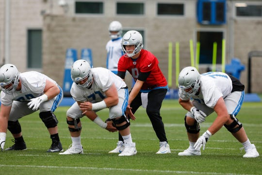 Lions quarterback Matthew Stafford prepares to take the snap from offensive guard Frank Ragnow during practice on Thursday, June 13, 2019, in Allen Park.