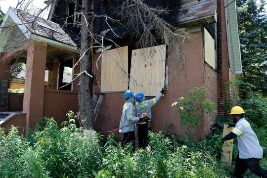 In a photo from Tuesday, June 11, 2019, members of the Detroit's Board Up Brigade board up a vacant home in north Detroit.