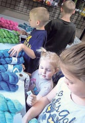 Helping their mom, Ariel Bishop, owner of AJHC Wools, put labels on hanks of hand-dyed yarn are (from bottom) Austyn, 7; Lilly Anne, 3; Wyatt, 8, and Kaden, 10.