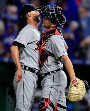 Tigers closer Shane Greene, left, and catcher John Hicks, right, celebrate the win and Greene's 20th save.