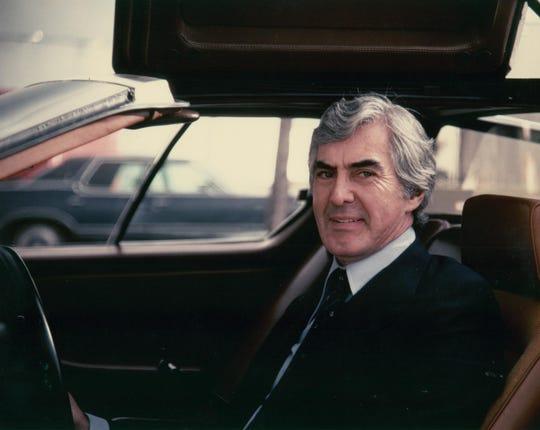 John DeLorean in the driver's seat of his famous DeLorean sports car.