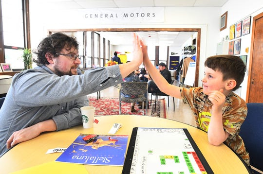 'Beyond Basics' tutor Chris Schahfer gives a  high-five to Declan Williams, 7, as they work on reading skills. Beyond Basics, a non-profit tutoring company, wants to reach 10,000 high schools student in Detroit through a three-year, $33 million campaign.