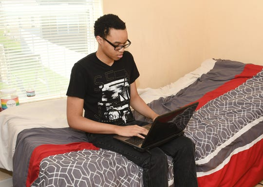 Emmanuel Franklin works on his computer at home.  Despite dealing with daily chronic pain, he has earned his high school diploma.