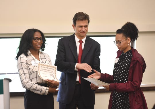 Aja Gaines, left, from Cass Technical High School, is presented with the Detroit News / Rosa Parks Scholar certificate by Detroit News Editor and Publisher Gary Miles as he shakes hands with fellow recipient Jade Rodriguez, from University Prep Science.