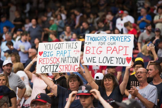 Fans hold up signs showing support for former Red Sox player David Ortiz.