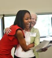 Maya Solomon of Cass Technical High School, left, hugs Deborah Lamm, widow of Detroit News editor and publisher Jon Wolman, as she receives the Jon Wolman scholarship on Thursday.