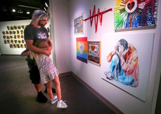 In a  Monday, June 3, 2019 photo, Bryan Formica, visiting from Cape Coral, Fla., embraces his daughter Marley, 8, as they visit the new 'Love Speaks' exhibit 'artists' reflections on the Pulse nightclub massacre.'