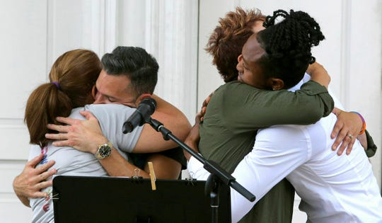 Participants in the reading of the 49 names of the victims in the Pulse nightclub massacre embrace at the conclusion of bells tolling, at First United Methodist Church in Orlando, Fla.
