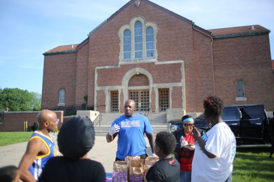 Aaron Salter, who was wrongfully incarcerated for murder for 15 years, hands out food outside Body of Christ Church on the west side of Detroit on June 7.  Salter has devoted his life after prison to helping others.