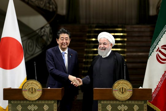 Japanese Prime Minister Shinzo Abe, left, and Iranian President Hassan Rouhani shake hands after their joint press conference at the Saadabad Palace in Tehran, Iran.