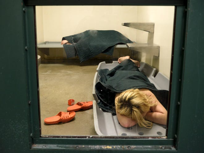 Two female inmates rest in an observation cell where they are being carefully monitored for mental health reasons at the Vanderburgh County Detention Center in Evansville, Ind., Thursday, May 23, 2019.