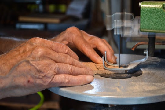 Tony Picciuto's 96-year-old hands guide the wood into the delicate shape of a cross.