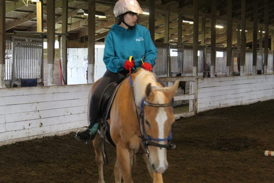 Beka Blohm, 16, of Port Clinton rides a horse at Riders Unlimited's Oak Harbor facility Monday.