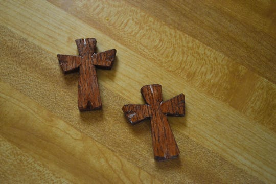 Two of the thousands of wooden crosses made by Tony Picciuto sit on his kitchen counter.