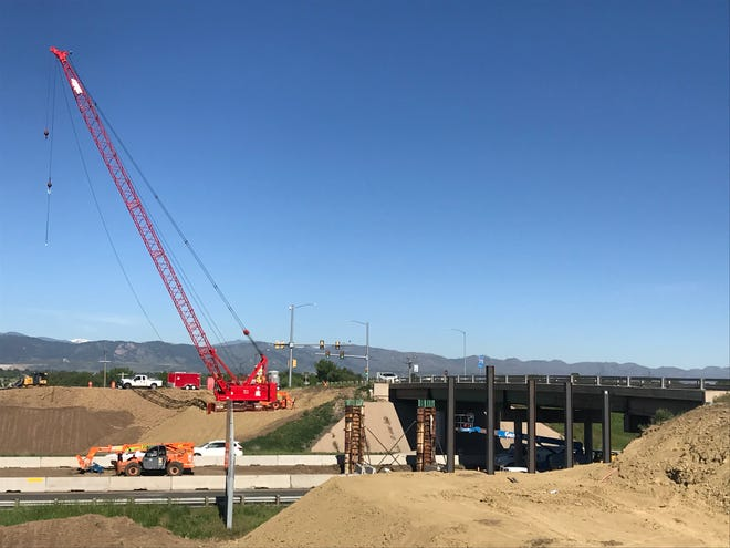 A crane readies to lift steel structures in place at Prospect Road bridge over Interstate 25 on Monday.