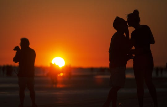 Visitors and Floridians flock to beaches in Fort Myers, Sanibel, Bonita Springs, Naples and Marco Island, among others in the region. This kiss between a couple was shared while watching a sunset on Fort Myers Beach.