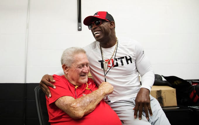 """""""I love you,"""" Deion Sanders tells his high school football coach Ron Hoover on Thursday before Sanders' PRIME TRUTH 7-on-7 football game at Bishop Verot High School in Fort Myers. Hoover coached Sanders at North Fort Myers High School. The all-star game features players from Texas and Lee County. All admission proceeds will go toward fundraising and building the Fort Myers TRUTH youth academic and sports non-profit organization, which is geared toward pushing children ages 5-12 toward sports as a vehicle toward success in life."""