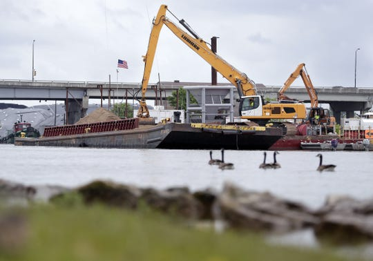 A sand barge at work on the Fox River marks the nearing completion of a multi-year effort to remove PCBs from the Fox River in Green Bay. The sand is being spread across the bottom of the river to serve as a cap to bury any chemicals not captured by dredging.