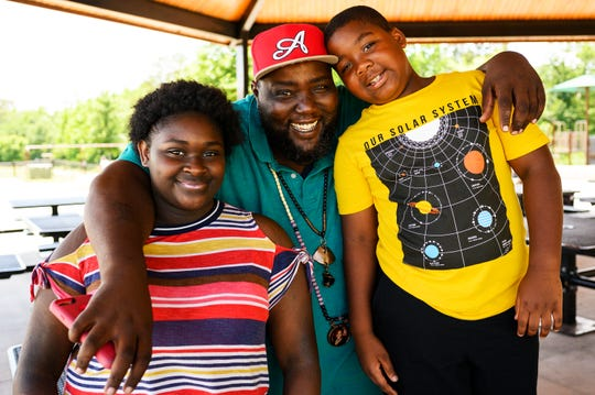 David Lomax poses for a portrait with his two children Janaija Sloan, 14, left, and Davion Cooley, 8, at Conestee Park Wednesday, June 13, 2019. Lomax, a single father, took sole custody of Davion after his son's mother died in December.  Lomax's  daughter lives with her mother and is spending the summer with her father.