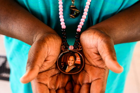 David Lomax holds a necklace decorated with a photograph of his partner, Carmen Nicole Cooley, Wednesday, June 13, 2019. Carmen died in a car accident in Dec. 2018, after which Lomax dedicated himself to being a single father to his son and daughter Janaija.