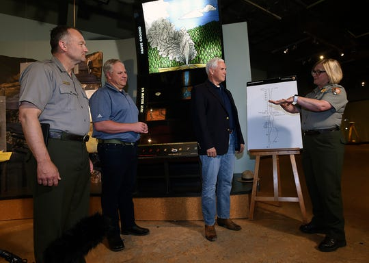 Vice President Mike Pence, Interior Secretary David Bernhardt and Yellowstone Superintendent Cameron Sholly get a briefing on the science of Old Faithful Geyser from ranger Rebecca Roland during a visit Thursday, June 13, 2019 in Yellowstone National Park in Wyoming. Vice President Mike Pence visited Yellowstone National Park Thursday to promote a plan to whittle away the more than $12 billion repair-and-maintenance backlog in parks across the U.S. (Larry Mayer/The Billings Gazette via AP)