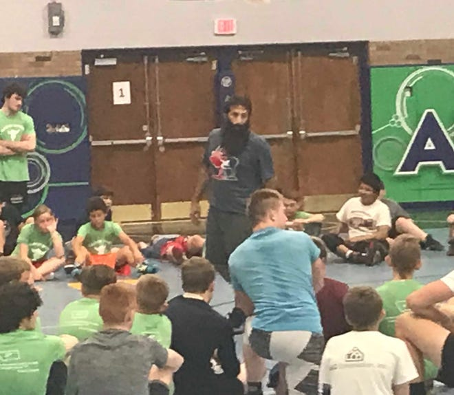 Mike Zadick, center, listens to a question asked by one of the campers at the Zadick Brothers wrestling camp this week at McLaughlin Center.