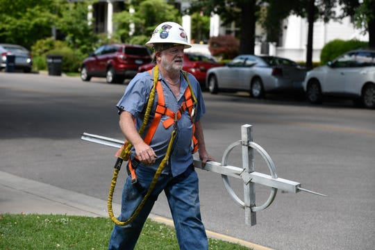 Rodney Whitlow, with Campbellsville Industries, walks to his work truck with the cross from the top of steeple from the Presbyterian Church of Henderson Thursday, June 13, 2019.