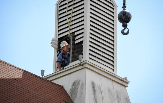 Timmy Milby with Campbellsville Industries uses a radio to help the crane operator maneuver next to a 39-foot-tall steeple they are removing from the Presbyterian Church of Henderson Thursday. The 1,500-pound structure will be refurbished and returned in 10 to 12 weeks, June 13, 2019.
