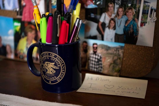 Rep. Susan Brooks, R-Indiana, stores pens in a mug from her time as deputy mayor of Indianapolis, next to a note from her daughter, Jess, and a bulletin board of family photos in her Washington D.C. apartment on June 13, 2019.