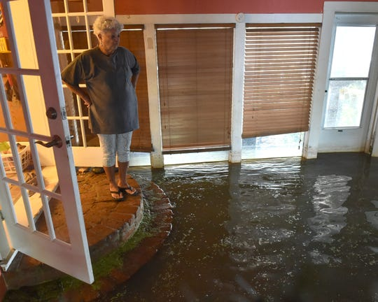 "Mary Huff looks at the water that has inundated a room in her home. ""Giving up my home that I've lived in for 41 years, that I've raised my children and grandchildren, in — and nobody cares. That's what's sad,"" she said."