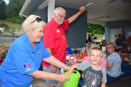 Lions Trish Wayne and Roy Wayne with Nathan Metz, 7, draw the first of many door prizes at the second annual Lions Club Shrimp Boil. June 8, 2019.