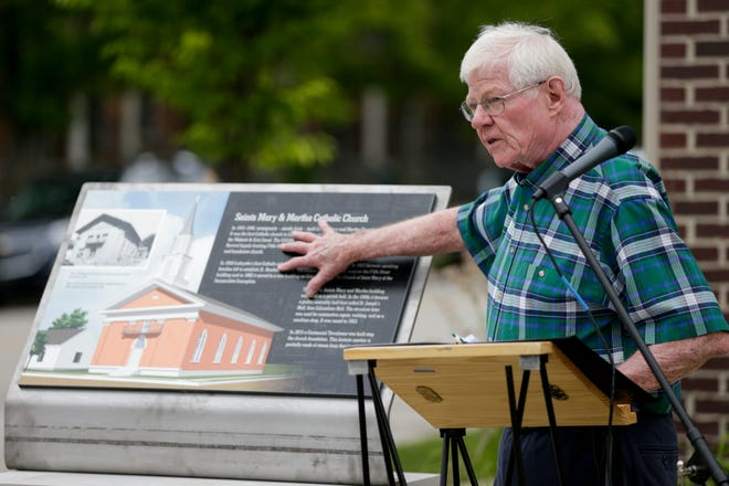 Michael Hunt places his hand on the historic marker at the former site of Saints Mary and Martha Catholic Church, Wednesday, June 12, 2019 in the Centennial Neighborhood of Lafayette. Saints Mary and Martha was the first Catholic Church in Lafayette.