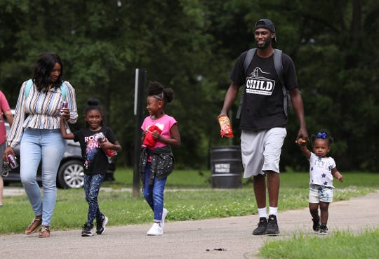 Detrick Ellery walks with his daughter Derian Ellery, 1, right, while his other daughters Demi Ellery, 6, center, and Demiah Ellery, 6, joined them on their way to the playground at Shawnee Park.  Demiah and Derian's mom Latasha Norfleet was at left.  Detrick is enrolled in the 4 Your Child parenting skills program.   June 12, 2019