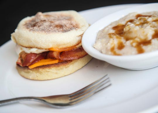 Highland Morning's The Loop's fried egg sandwich on an English muffin and grits of the day, which can feature toppings such as maple syrup.
