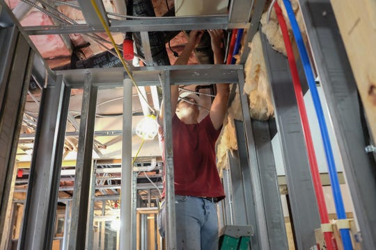 Bryce Smith works on the electrical system in the second floor apartments of the F.C. Mason building renovation in St. Johns Thursday, June 13, 2019.
