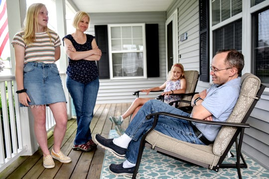 Christopher Lewis, far right, and, from left, his daughter Juliana, 14, his wife Jean, and other daughter Paige, 11, talk on the front porch of their home on Wednesday, June 12, 2019, in Williamston. Christopher started a blog 12 years ago, Dad of Divas, about how to be a father of daughters. He's interviewed over 800 dads of daughters and now has a Facebook group, Dads with Daughters, with 22,000 followers from around the world. His group page is now featured in a Facebook ad.