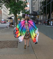 A woman in a colorful butterfly cape ran to escape the rain at last year's Michigan Pride Parade in downtown Lansing. The weather calls for about a 50 percent chains of rain throughout the day for Saturday's parade.
