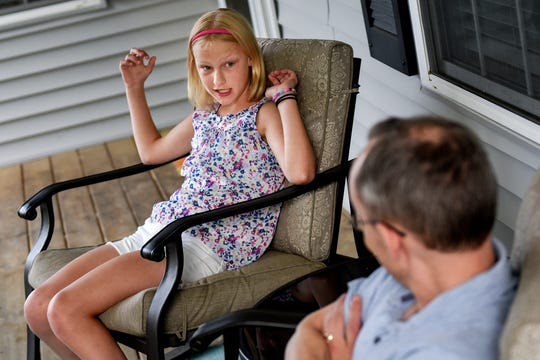 Paige Lewis, 11, left, talks with her father Christopher Lewis at their home on Wednesday, June 12, 2019, in Williamston.