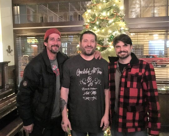 Antonio M. Lujan (far left) stands with friends Charles (center) and Zachary Lulloff (far right) at Moore's Irish Pub in Manitowoc around the holidays.