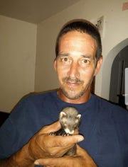 Antonio M. Lujan holds a ferret.
