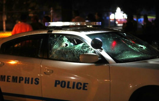 A Memphis police car with its windows smashed sits in the area of a shooting involving U.S. Marshals in Frayser on June 12, 2019.