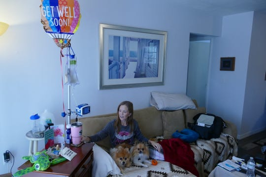 Kerrie (Grganto) Wallace sits at home with her dogs Bella and Leo while a machine connected to her abdomen feeds her nutrients, bypassing her stomach. She was discharged from the hospital last Friday.