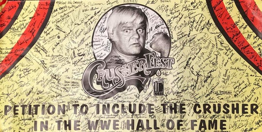 "A banner that said ""Petition to include The Crusher in the WWE Hall of Fame"" was put out at the information booth  for attendees to sign during Crusherfest."