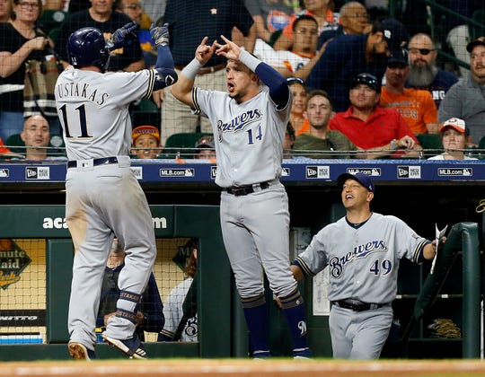 Hernan Perez is the first to greet Mike Moustakas at a happy Brewers dugout after his two-run home run in the top of the 14th inning lifted Milwaukee to a 6-3 victory over Houston.