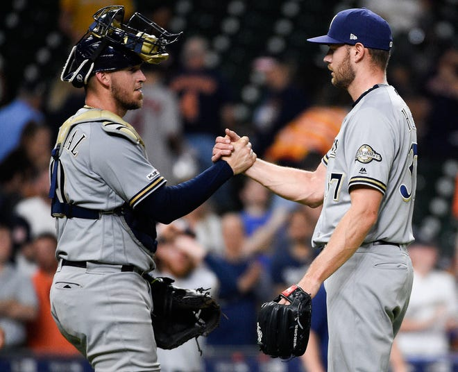 Reliever Adrian Houser and catcher Yasmani Grandal shake hands after the final out of the Brewers' 6-4 win in 14 innings over the Astros on Wednesday night. Houser, who picked up the victory, was part a relief effort from Milwaukee's bullpen that pitched seven shutout innings, allowing just one hit with six walks and eight strikeouts.