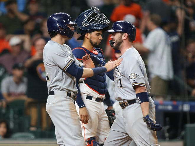 Mike Moustakas (right) is greeted by Christian Yelich after his two-run blast in the 14th inning propelled the Brewers to a 6-3 victory over the Astros.