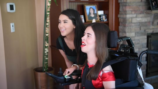 """Victoria Rossi (right),  a senior at Hanover Park High School who requires a wheelchair for mobility due to muscular dystrophy, , had a prom dress custom-made by another high school senior, Kylie McRobie (left) of Scarsdale, NY, through the nonprofit foundation, Runway for Dreams. The dress was inspired by Julia Roberts' dress in """"Pretty Woman."""" Rossi is photographed in her home on Wednesday, June 12, 2019, in East Hanover."""