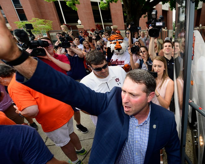 Auburn coach Butch Thompson waves to the fans as the team departs for the College World Series in Omaha, Wednesday, June 12, 2019, in Auburn, Ala.